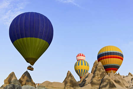 Hot air balloons captured coming over the limestone ridge near Goreme, Caapadocia, Turkey   photo