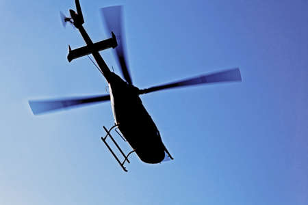 Generic silhouette of an helicopter caught  in flight against a clear blue sky