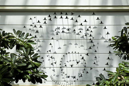 Interior feature over a pond, backgrop of metal cut out birds in stages of flight with plants in the foreground