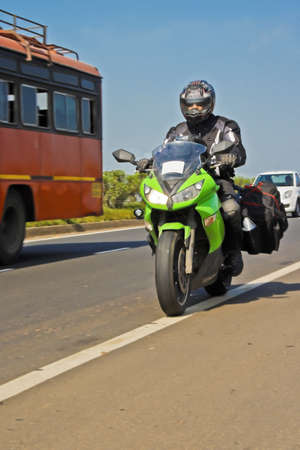 indore: Indian motor cyclist on tour on the NH3 Mumbai to Indore Agra Road with protective clothing and fully laden with tank bacg and saddle bags Stock Photo