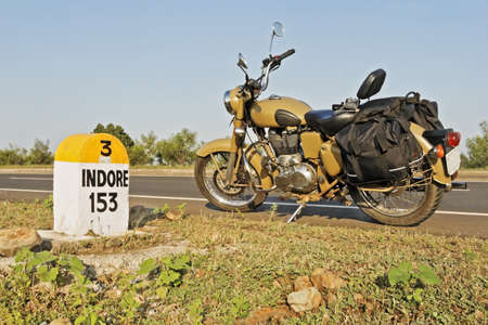 Indian motorcycle parked on NH3 Mumbai Agra Road at the 153kms milestone in the hinterlands of India