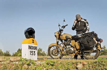 Motorcyclist on an open road in India on his way to Indore using a mobile phone  Helmet on milestone for 153 kilometers