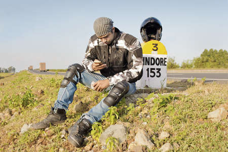 Young Indian man on travels by motorcycle checking for messages on his mobile at a milestone  Shot location, Maharashtra, India photo