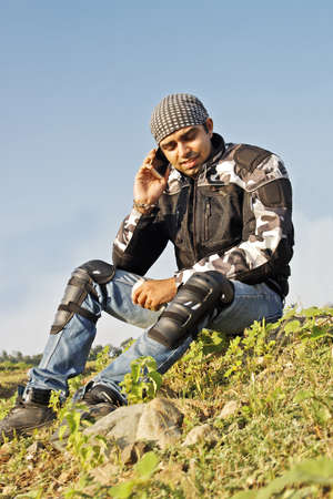 indore: Young adult male in bikers gear sat at the roadside using a moblie phone  Generic shot, location India Stock Photo