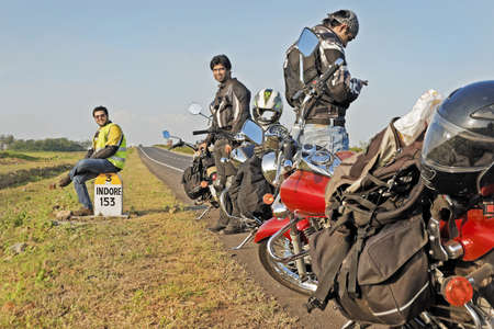 madhya: Indian motorbikers on tour taking a rest at the 153 kilometers to Indore milestone on the NH3 Mumbai to Agra Road  Stock Photo