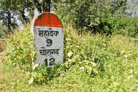 mahadev: Milestone indicating 9 kilometers to Mahadev  Shot location Pacharchi, Madhya Pradesh, India