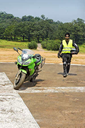 embark: Indian bicker striding towards his superbike to embark on next ride  Parked on a heliport, shot location Pachmarhi, Madhya Pradesh, India  Rural countryside area with greenery and blue skies Stock Photo