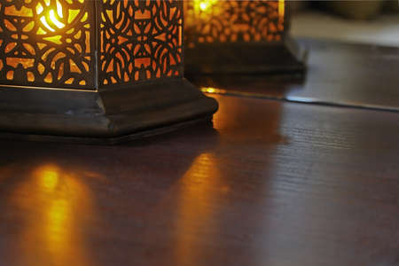 Amber colored buld in a oriental eastern design table casts beams over table surface and reflections in mirror