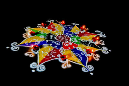 Rangoli, hand sketched patterns and designs filled colored powder are a common item in hindu homes at divali and new year usualy accompanied by ghee  butter  burning candles called diva Stock Photo - 16442404