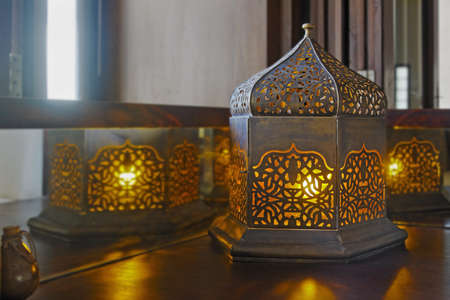 switched: Generic oriental table lamp set on corner table with yellow bulbs switched on giving amber glow