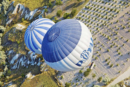 Diagonal aerial shot of two hot air balloons on a low level flight path over the interesting limestone agricultural land of Cappadocia, Turkey June 29 2011 Stock Photo - 17522501