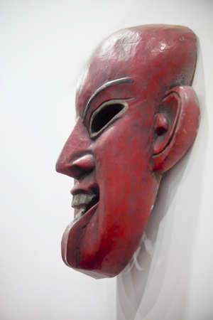 Vertical take of a generic mounted hand carved smiling mask  SHot location India