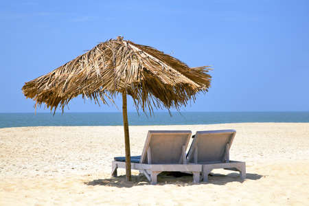 A generic tropical deserted beach with loungers under a coconut leaf parasol  Blue sky, ocean, gentle surf sound and clean sandy beach  Location, Goa India