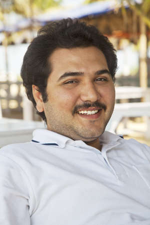 combed: vertical portrait of a smiling young adult male, combed back hair, mustache, un shaved, celebrity look a like, showing teeth, wearing white pole shirt, in the shade outdoors leaning back in a relaxed posture