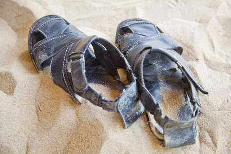 fastened: horizontal landscape of a pair of generic old black leather sandals, still fastened left in sand  location of this shot was goa, india Stock Photo