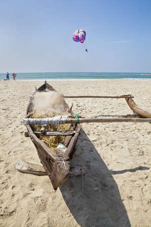 bathers: Horizontal landscape of a Goan beach in India with a moored fishermans boat on a sandy beach, bathers about to undress an get in the ocean while a paraglider drifts by