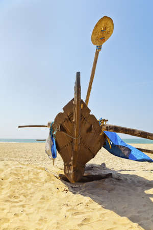 Vertical portrait of abstract fishermans cataran with an oar   paddle on a sandy beach and under blue skies  Generic shot of the east, this location is in Goa, India photo