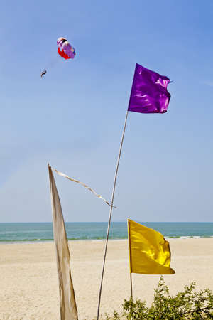 Vertical generic shot of colorful flags blowing in the breeze outside a shack restaurant in Goa India  Sandy beach with surf and coastline, picturesque idyllic scene and a paraglider passes by in the distance
