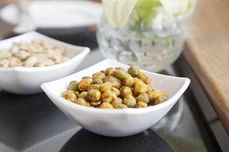 Horizontal studio setup of a bowl of dehyrated roasted spicy peas in a white square designer procelain square bowl on a table top with peanut bowl in background