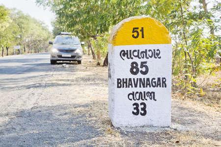 hindues: Horizontal paisaje rural en Gujarat India incorporaci�n de 85 kilometros a Bhavnagar hito y marca de tierra en la carretera costera de Dwarka un pueblo religioso para los hind�es monovolumen estacionado con las luces de cabeza encendido