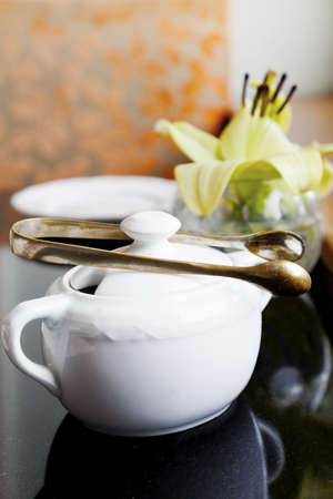 Vertical Interior corner detail of black top table with tea and coffee utensils of sugar bowls and bud vase with a lily by a window Stock Photo
