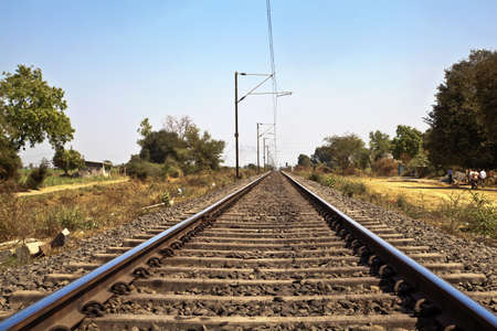landscape of railroad tracks in Indian cutting acrosss the rural countryside along the outskirts of o Gujarat village near the city of Surat  Typical scenec with litter thrown around and locals walking close by Stock Photo