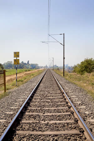 Vertical landscape of railroad tracks in Indian cutting acrosss the rural countryside along the outskirts of o Gujarat village towards the city of Surat  Typical scene with litter thrown around and locals walking close by