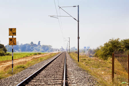 Horizontal landscape of railroad tracks in Indian cutting acrosss the rural countryside along the outskirts of o Gujarat village towards the city of Surat  Typical scene with litter thrown around   Stock Photo
