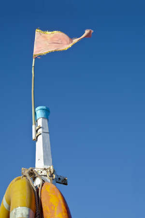 Dwarka Roadtrip  Concept of Rich blue sky split by a white mast bearing yellow life bouys and a pink frayed flag  Generic shot location Bet Dwarka, Gujarat, India