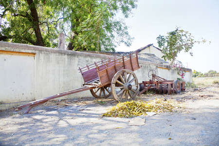 gujarat: Landscape at the outskirts of an Indian hinterlands village of a wall lined with farm machinery and parked bullock cart under the shade of trees Stock Photo