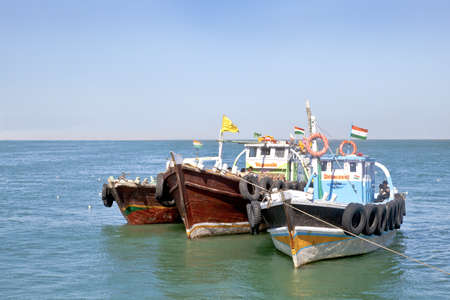 uncluttered: Horizontal seascape of Indian passenger ferries moored under a blue sky at Bet Dwarka, Gujarat, India