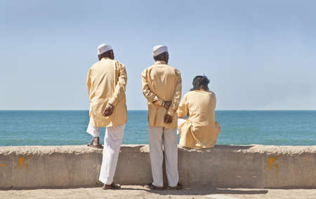 unifrom: Dwarka Roadtrip  Horizontal portrait of three clerics in formal attire looking  out to the horizon of the Arabian Sea  The location of this conceptual shot was at the beach and promanade at Dwarka, Gujarat, India near the Krishna Temple
