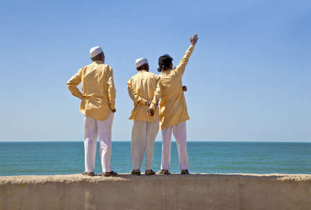 Dwarka Roadtrip  Horizontal portrait of three clerics in formal attire looking and pointing out to the horizon of the Arabian Sea  The location of this conceptual shot was at the beach of Dwarka Bay, Gujarat, India near the Krishna Temple Stock Photo - 18925182