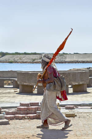 vetical: Vetical capture of a religous hindu man holyman walking, carrying a flag from his pilgrimage to the Krishna Temple at Dwarka in Gujarat India Febuary 27 2103 Editorial