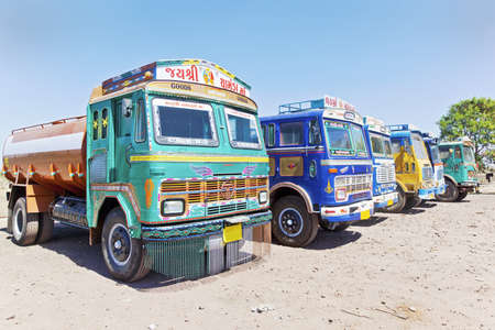 Colorful Indian heavy goods vehicles parked up at  Dhabha  Indian truck stop  in the mid day sun while the driver and crew take an after noon nap from the heat of the Indian sun