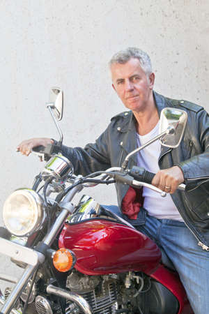 Portrait of a Caucasian motorbiker in casual attire and tight lipped looking into lens sat on a red cruiser  Generic shot location was Bombay India photo