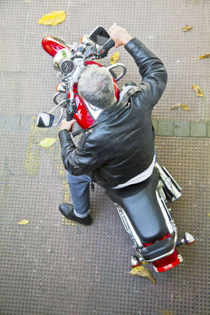 Diagonal aerial viewpoint of a stationary red motorbile and a grey haired rider in leather jacket, denim jeans and boots on a tied floor with fallen autumn leaves  Generic shot taken in Bombay India photo