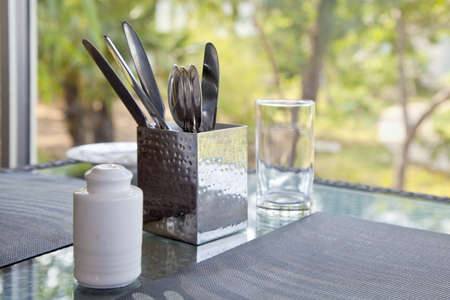 Horizontal capture of a dinner table waiting to be properly set at a picture window looking onto a garden  Place mats, cutlery knife and spoon, pepper pot and water glass
