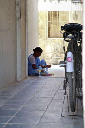 newsprint: Vertical capture of an Indian maid sat on the floor in the shade inside an alleyway having lunch which has been wrapped in newsprint  Typical shot in Indian with bicycle parked close by