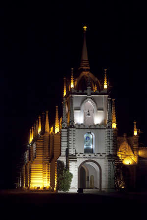 Vertical portrait of Mae de Dues Church Goa India taken from the public road surrounding the property, generic night scene of the Portugese inspired religious architecture Stock Photo