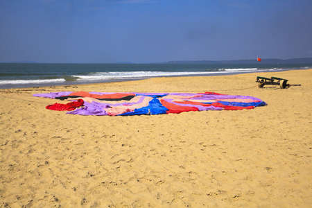 Generic horizontal beach and ocean landscape of a parachute laid flat on the sandy Uttorda Beach at Goa, drying in the hot Indian sun  Red tide flag and trolley with waves spalshing on the shoreline