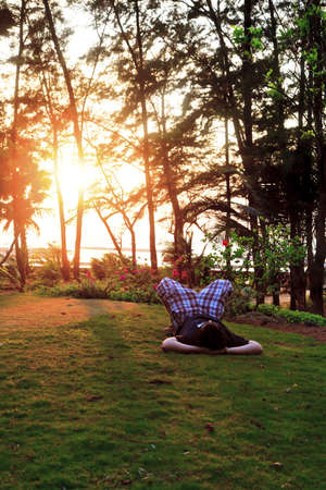 Vertical color portrait of man laying on garden lawn, arms acting as support for head, point of view at his head, kness folded up, sunset shininng through the trees, location of shot Manori, Bombay, India