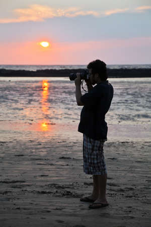 Vertical color portrait of young man taking pictures at sunset on the beach at Manori, Bombay, India Stock Photo