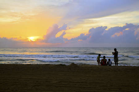 Horizontal color landscape of an Asian Indian family down on the beach early to catch the sunrise and family photographs  Man, woman and two kids captured at Manaputti Beack, Pondicherry, India