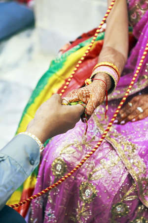 Vertical color capture taken at a hindu wedding ceremony where couple hold hands containing betal leaf, ceremonial red and yellow cord binds them tin matrimony whilst the rituals are being performed by clergy
