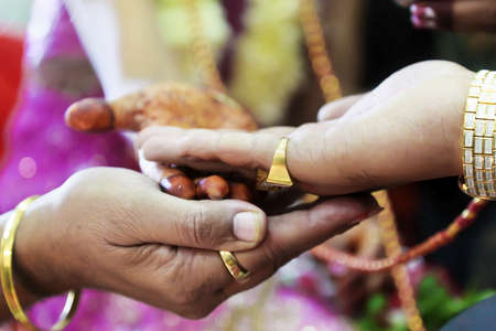 daughter in law: Horizontal color capture hindu wedding   Part of the ceremony is that the mother in law supports the hand of her daughter who in turn supports the grooms hand whilst the rituals are being performed by clergy Stock Photo