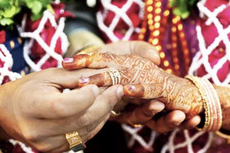 anillo de boda: Color Horizontal capture tomada en una boda hind� en Surat India sesi�n de fotos despu�s de la ceremonia del feliz novio poniendo el anillo de bodas en la m�s fina de las novias de las c�maras vida est� a punto de comenzar