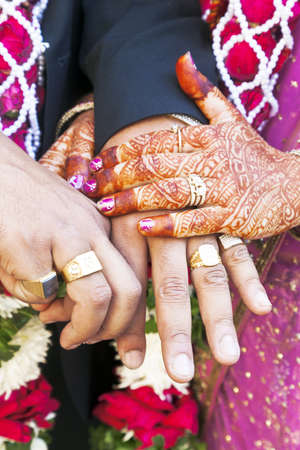 Vertical color portrait taken at a hindu wedding in Surat India  Photo session after the cerempny of the happy hand holding couple displaying their rings of matrimony and the brid lays her claim
