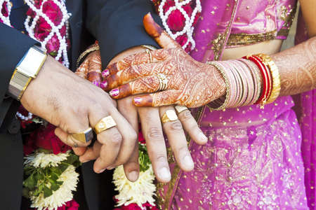 Horizontal color capture taken at a hindu wedding in Surat India  Photo session after the cerempny of the happy hand holding couple displaying their rings of matrimony and the brid lays her claim