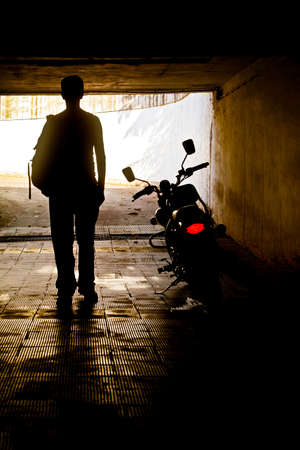 ruck sack: Vertical silhouette concept capture of a man in a vest with ruck sack back pack near his motorcycle which has its tail slights swtiched on in a tunnel Stock Photo